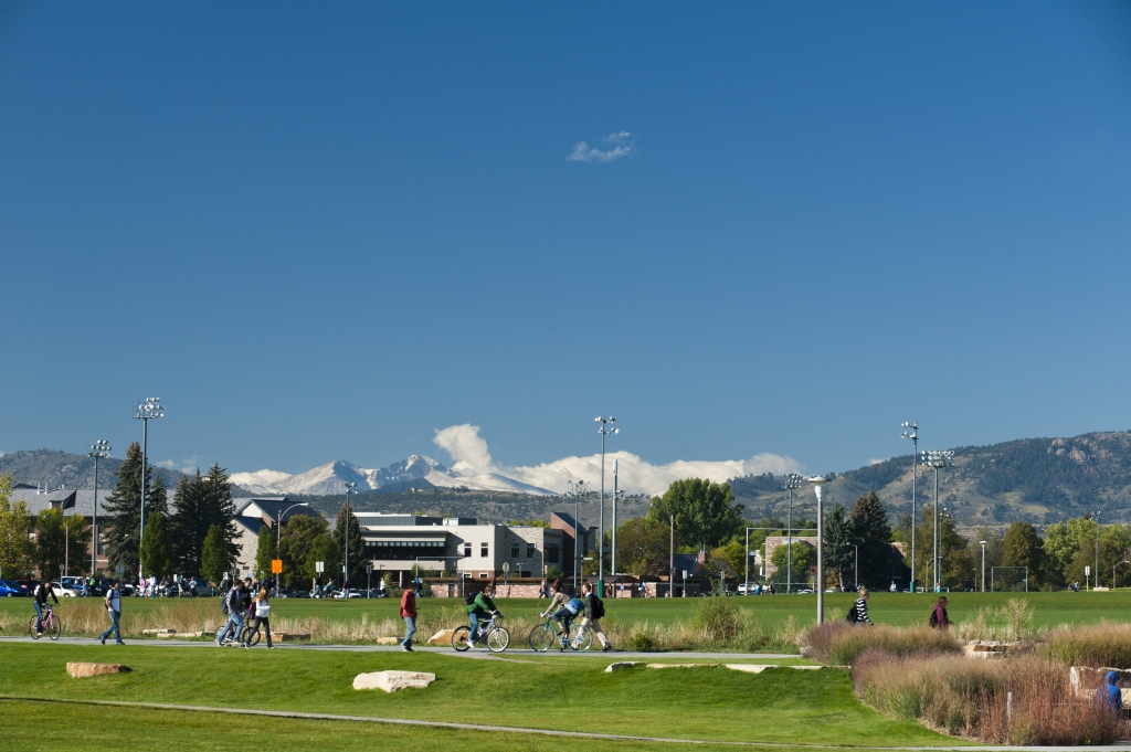 Students walk on the West Lawn of the Colorado State University in the with snow on Longs Peak in the background.